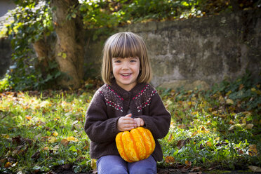 Portrait of smiling little girl with pumpkin - LVF002057