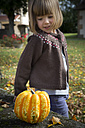 Little girl crouching besides a pumpkin in the garden - LVF002054
