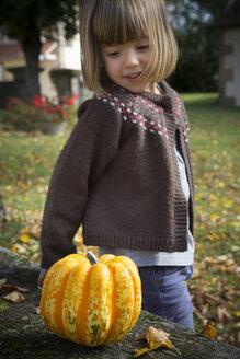 Little girl crouching besides a pumpkin in the garden - LVF002054
