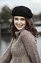 Portrait of happy young woman wearing beret and knitted dress - GDF000494