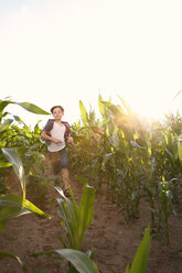Boy running through maize field at backlight - FKIF000064