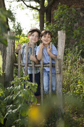 Portrait of two little boys standing behind a wooden fence - FKIF000040
