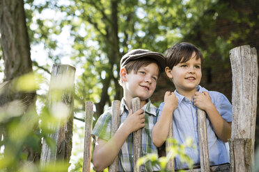Portrait of two little boys standing behind a wooden fence - FKIF000042