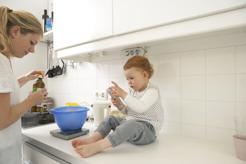 Little girl sitting on kitchen counter with smartphone while her mother baking - FSF000238