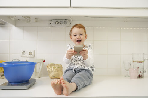 Laughing little girl sitting on kitchen counter with smartphone - FSF000247