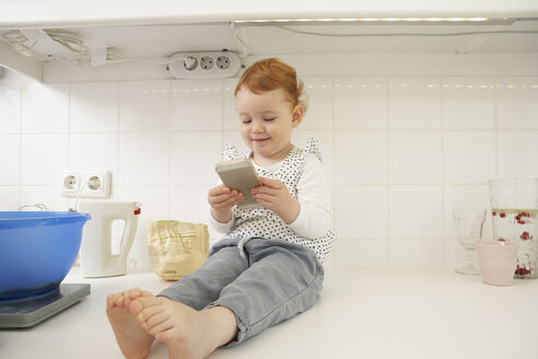 Little girl sitting on kitchen counter with smartphone - FSF000248