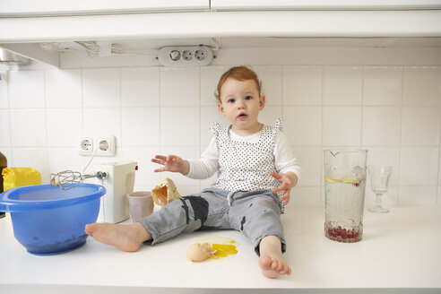 Little girl sitting on kitchen counter with broken egg - FSF000205