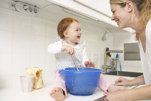 Mother and little daughter baking cake together in their kitchen - FSF000216
