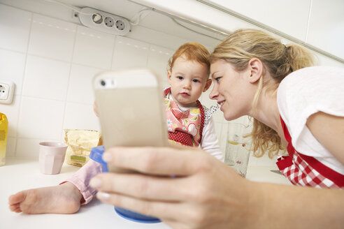 Young woman taking a selfie with her little daughter in their kitchen - FSF000217