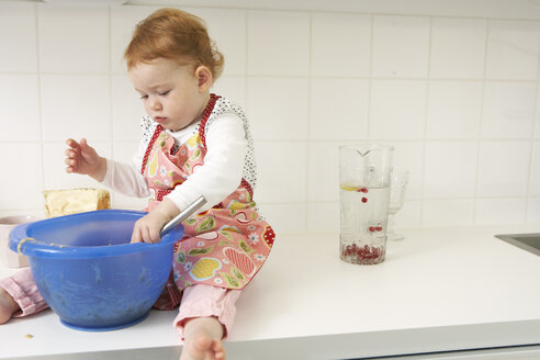 Little girl sitting on kitchen counter with mixing bowl - FSF000218