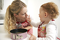 Mother and little daughter baking cake together in their kitchen - FSF000220
