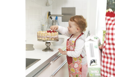Mother and little daughter baking cake together in their kitchen - FSF000224