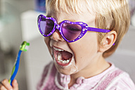 Portrait of little girl wearing sunglasses brushing teeth - JFEF000476