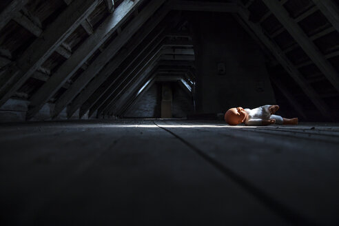 Doll lying at empty dark attic - JFEF000481
