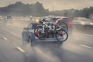Car with bicycles on motorway in rain - FR000016