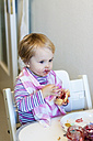 Little girl with bib trying to eat jam roll - JFEF000504