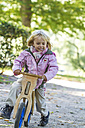 Little girl driving on balance bicycle - JFEF000512