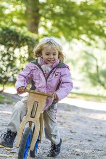 Little girl driving on balance bicycle - JFEF000512
