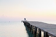 Spain, Balearic Islands, Cala de Muro, one man walking on a jetty - MS004318