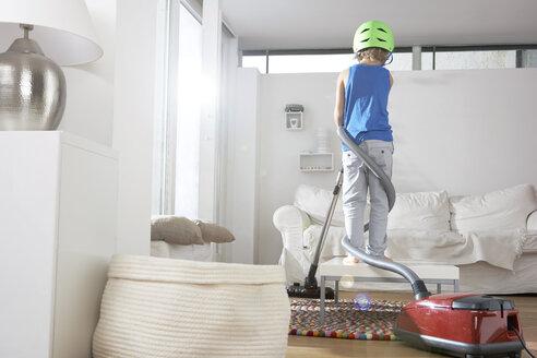 Boy in living room tangled in vacuum cleaner - FSF000253