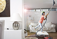 Boy in living room hoovering the ceiling - FSF000274