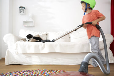 Boy in living room hoovering the sofa with cat - FSF000278