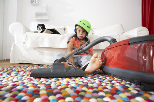 Exhausted boy in living room with cat and vacuum cleaner - FSF000280