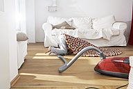Boy in living room hoovering under carpet - FSF000256