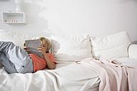 Boy lying on couch using digital tablet - FSF000260