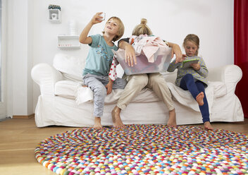 Exhausted mother with laundry basket on couch with children using digital tablet and cell phone - FSF000270