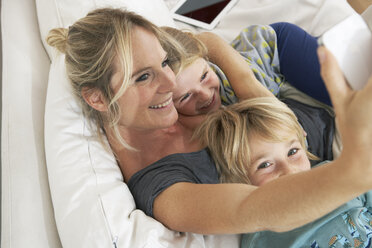 Happy mother, daughter and son on couch taking a selfie - FSF000266