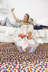 Mother, daughter and son on couch taking a selfie with laundry basket on floor - FSF000269