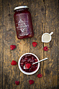 Glass and bowl of red fruit jelly, milk and raspberries on dark wood - LVF002051