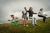United Kingdom, England, Cornwall, Children jumping from stone - PAF001024