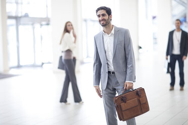 Smiling businessman with briefcase in lobby - ZEF007943