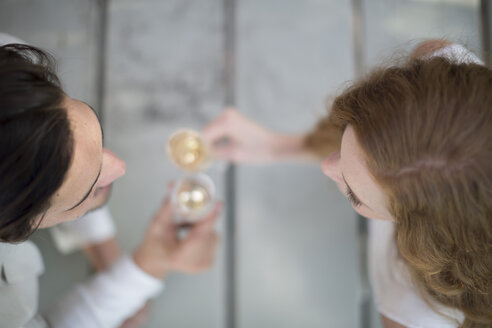 Overhead view of couple outdoors clinking champagne glasses - ZEF007952