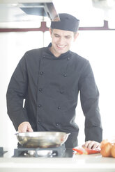 Smiling chef cooking in kitchen - ZEF007955