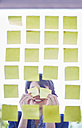 Female creative professional behind glass pane with adhesive notes covering her eyes - ZEF001497