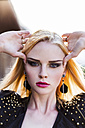Portrait of rouged blond woman with hands on her head - DAWF000207