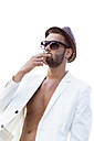 Smoking young man wearing hat, sunglasses and white jacket on bare chest - DAWF000228