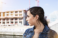 Germany, Berlin, profile of young woman in front of construction site - FKF000708