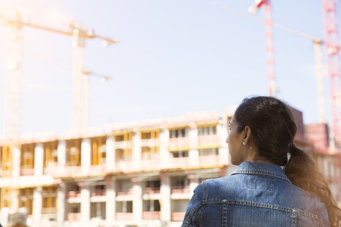 Germany, Berlin, young woman standing in front of construction site - FKF000711