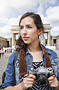 Germany, Berlin, portrait of female tourist with camera - FKF000716