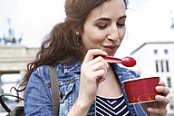 Germany, Berlin, portrait of young female tourist eating ice cream near Brandenburg Gate - FKF000722