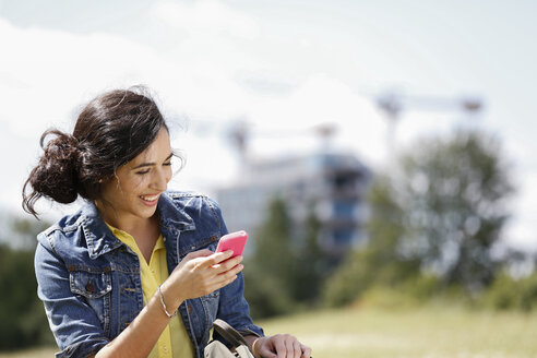 Germany, Berlin, portrait of happy young woman using her smartphone - FKF000731