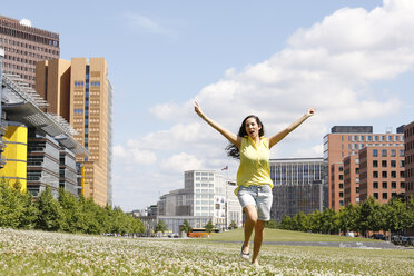 Germany, Berlin, happy young woman dancing on a meadow near Potsdam Square - FKF000737