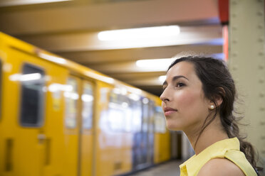 Germany, Berlin, young woman waiting at underground station - FKF000740