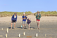 Mother and three children playing Kubb on the beach - LAF001193