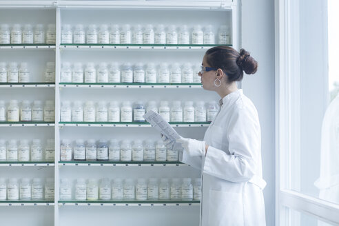 Young female scientist working in a chemical lab - SGF000895
