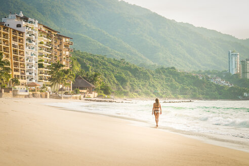 Mexico, Puerto Vallarta, woman wearing bikini walking at the Punta Negra beach - ABAF001547